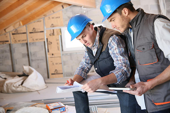 two construction workers review the plans